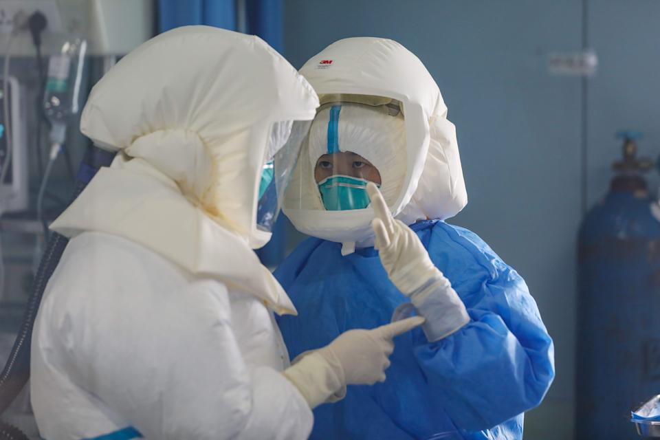 Two medical staff work in the negative-pressure isolation ward in Jinyintan Hospital, designated for critical COVID-19 patients, in Wuhan.
