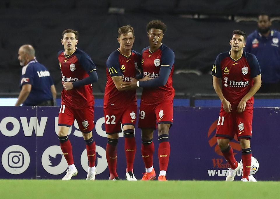Kusuni Yengi (pictured second on right) celebrates after scoring a goal during the A-League match between the Melbourne Victory and Adelaide United at Marvel Stadium, on March 13, 2021.