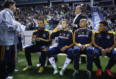 Los Angeles Galaxy midfielder Robbie Rogers (14) sits on his team bench in front of head coach Bruce Arena before their MLS soccer game against the Seattle Sounders in Carson, California May 26, 2013. REUTERS/Danny Moloshok