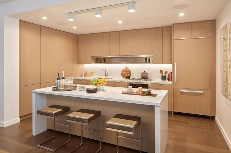 A typical kitchen in a condo unit at The Avery features textured wood paneling, marble counters, and Miele appliances.