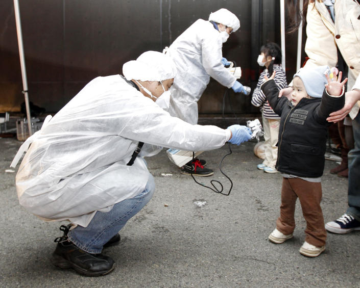 Officials in protective gear check for signs of radiation on children who are from the evacuation area near the Fukushima Daini nuclear plant in Koriyama, March 13, 2011. Japanese Chief Cabinet Secretary Yukio Edano confirmed on Saturday there has been an explosion and radiation leakage at Tokyo Electric Power Co's (TEPCO) Fukushima Daiichi nuclear power plant. The biggest earthquake to hit Japan on record struck the northeast coast on Friday, triggering a 10-metre tsunami that swept away everything in its path, including houses, ships, cars and farm buildings on fire.   REUTERS/Kim Kyung-Hoon (JAPAN - Tags: DISASTER ENVIRONMENT ENERGY IMAGES OF THE DAY)   FOR BEST QUALITY IMAGE: ALSO SEE GF2E88U0STU01.