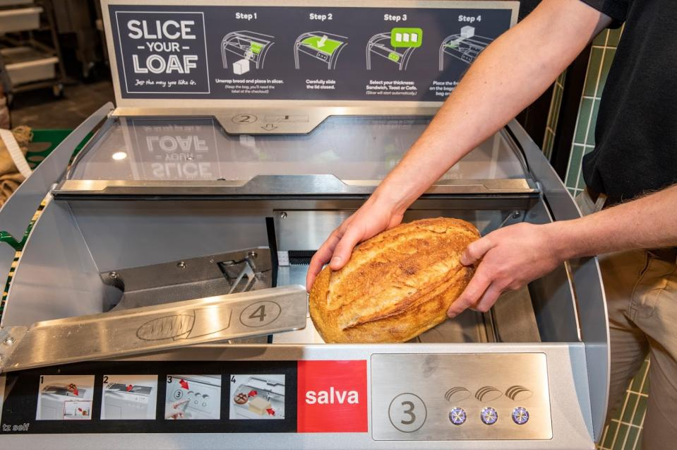 A man uses the bread slicer in Woolworths to cut a loaf of bread.