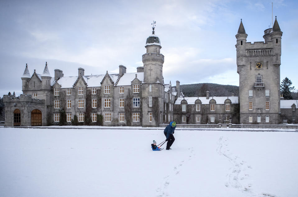 Geraint Stone pulls his two-year-old son Arthur on his sledge across the snow-covered lawn in front of Balmoral Castle, Royal Deeside. The Met Office has issued a yellow weather warning for ice and snow across Scotland. (Photo by Jane Barlow/PA Images via Getty Images)