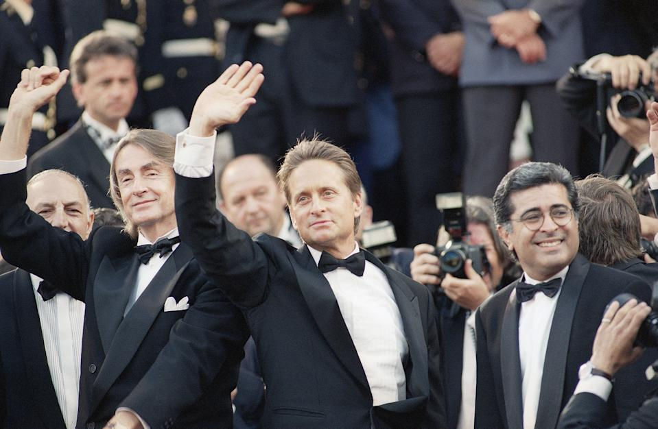 """American actor Michael Douglas, right, waves to the crowd as he arrives for the screening of his movie """"Falling Down"""", directed by Joel Schumacher, left, during the 46th International Film Festival in Cannes on Saturday, May 22, 1993. (AP Photo/Gilbert Tourte)"""
