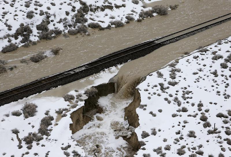 Train tracks are flooded Wednesday, Feb. 8, 2017, after the 21 Mile Dam near Montello, Nevada, broke and caused flooding to the Union Pacific railroad line near Lucin and flooded the town of Montello. The dam break forced delays or rerouting for more than a dozen freight and passenger trains on a main rail line that runs through the area, said Union Pacific spokesman Justin E. Jacobs. (Stuart Johnson/ The Deseret News via AP)
