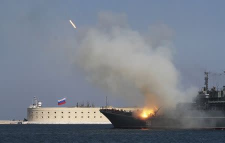 A Russian warship fires during celebrations to mark Navy Day in the Crimean port of Sevastopol July 27, 2014. REUTERS/Stringer
