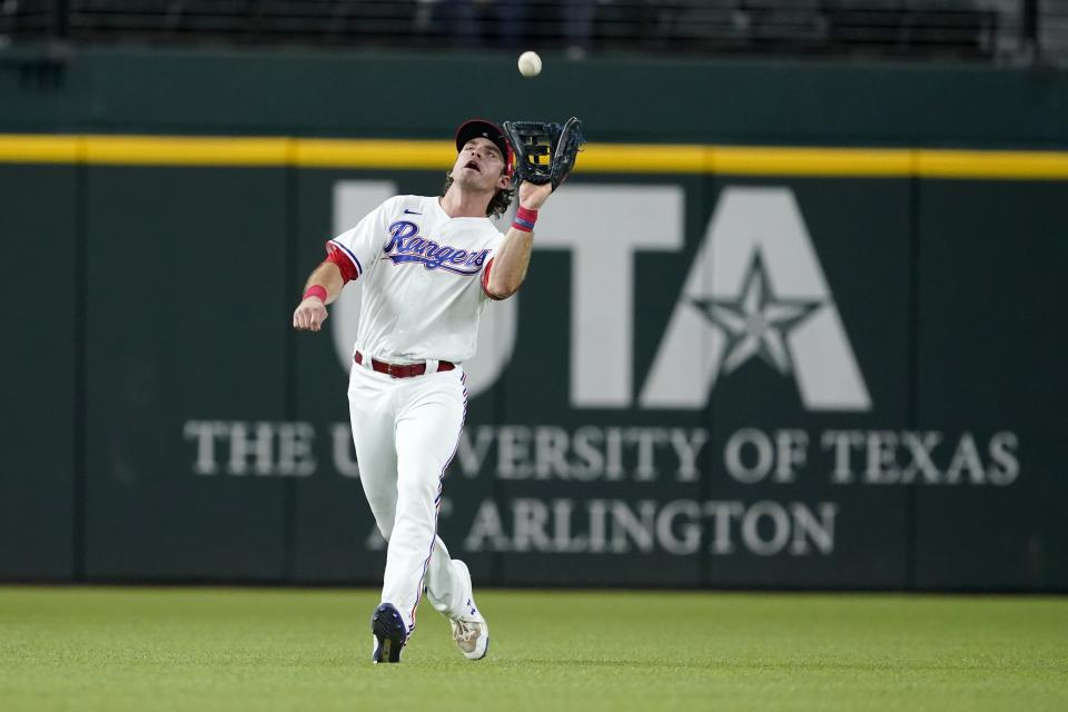Texas Rangers left fielder DJ Peters reaches up to catch a fly out by Los Angeles Angels' Jared Walsh in the sixth inning of a baseball game in Arlington, Texas, Tuesday, Sept. 28, 2021. (AP Photo/Tony Gutierrez)