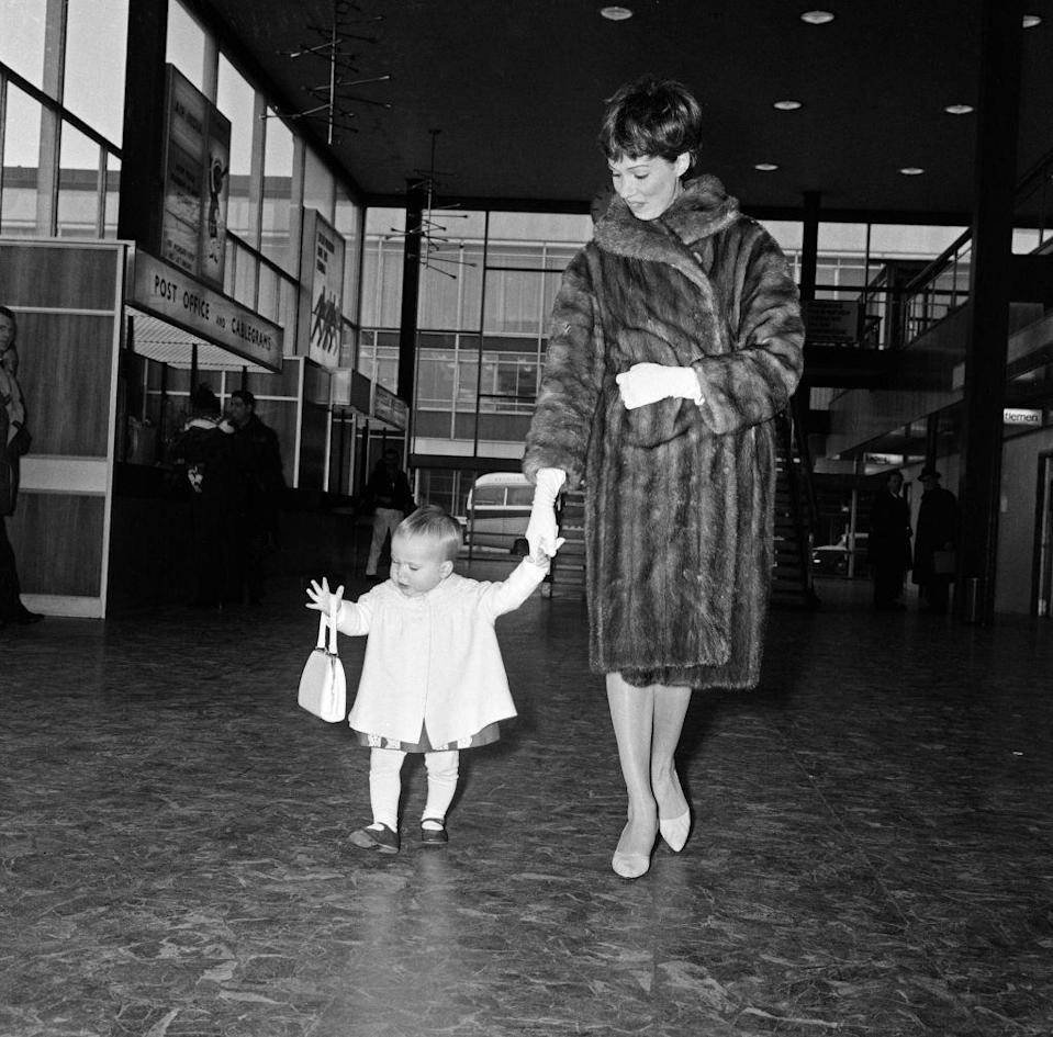<p>Julie holds the hand of her toddler, Emma, as they walk around the airport in London in 1964. The actress even gave her daughter her handbag to play with. </p>