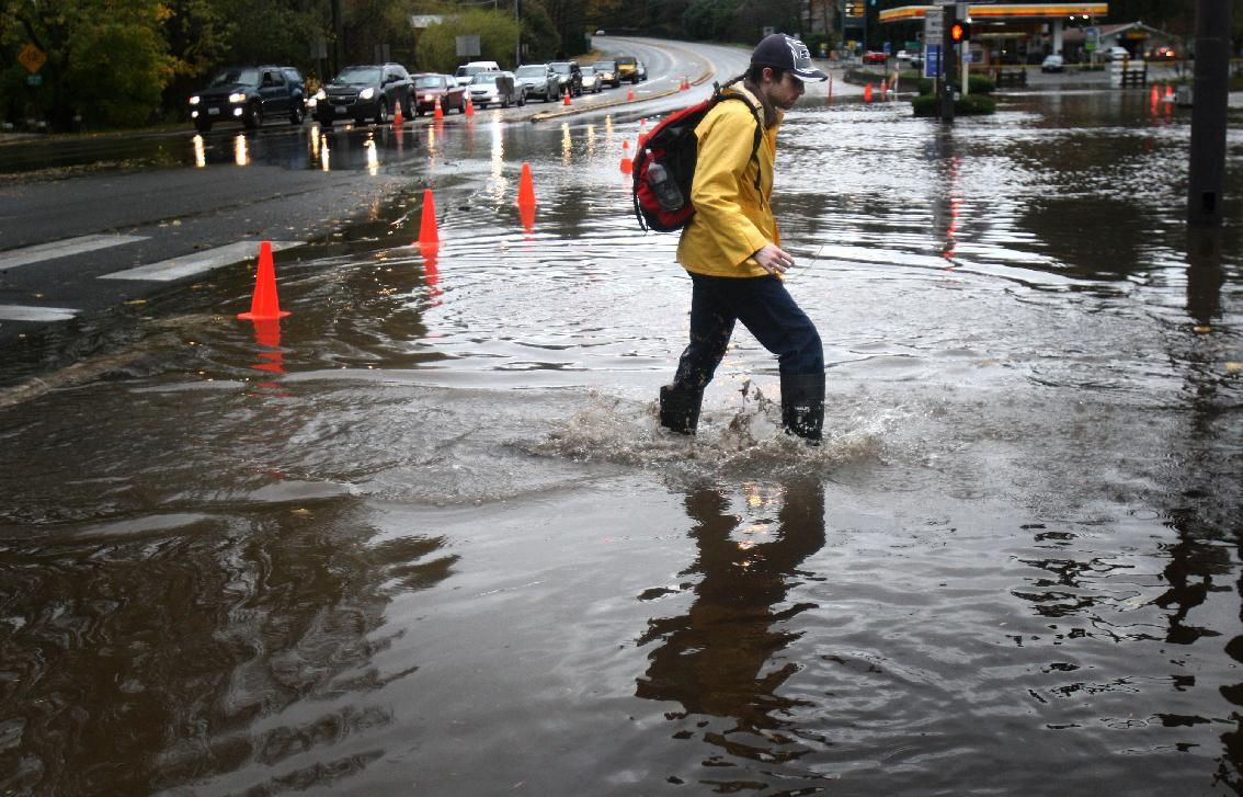 A pedestrian makes his way across a flooded section of Bothell Way NE in Lake Forest Park in Seattle, during a significant rainfall on Monday, Nov. 19, 2012. Residents in Washington and Oregon are bracing for expected river flooding after heavy rain and winds that caused sporadic road closures, power outages and at least one death. The wet weather is expected to continue throughout the week, after hurricane-strength winds battered both states along the coast. (AP Photo/seattlepi.com, Joshua Trujillo)