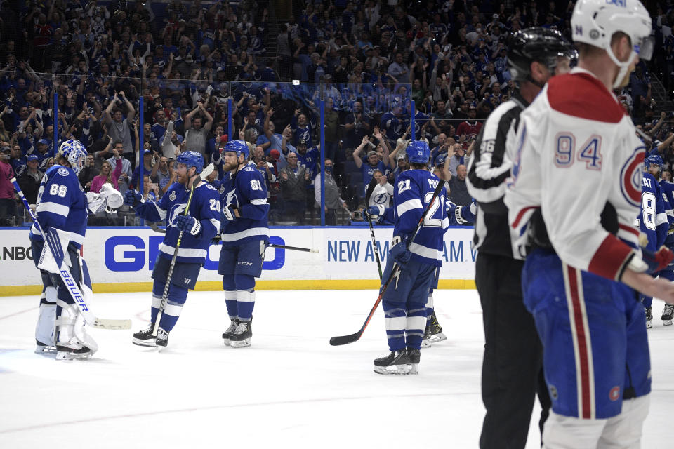 Montreal Canadiens right wing Corey Perry (94) skates off the ice as Tampa Bay Lightning goaltender Andrei Vasilevskiy is greeted by teammates after the third period in Game 2 of the NHL hockey Stanley Cup finals, Wednesday, June 30, 2021, in Tampa, Fla. The Lightning won 3-1. (AP Photo/Phelan Ebenhack)