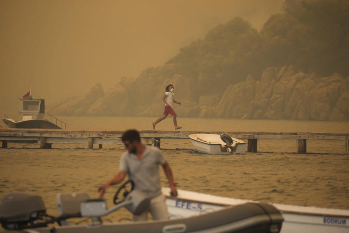A man runs from smoke-engulfed Mazi area as wildfires rolled down the hill toward the seashore, in Bodrum, Mugla, Turkey, Sunday, Aug. 1, 2021. More than 100 wildfires have been brought under control in Turkey, according to officials. The forestry minister tweeted that five fires are continuing in the tourist destinations of Antalya and Mugla. (AP Photo/Emre Tazegul)