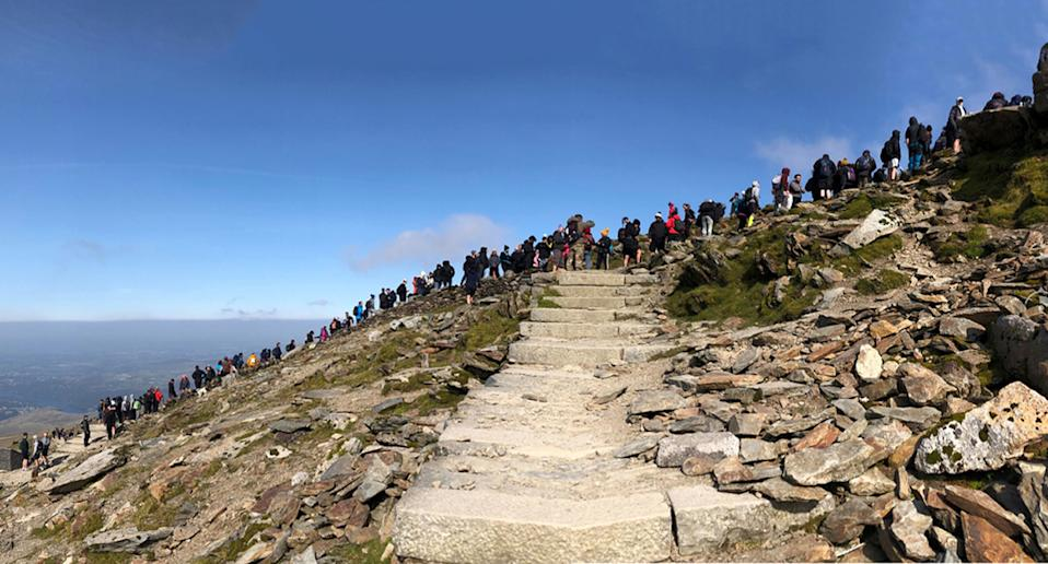 Dozens of people queue on the mountain top at Mount Snowdon