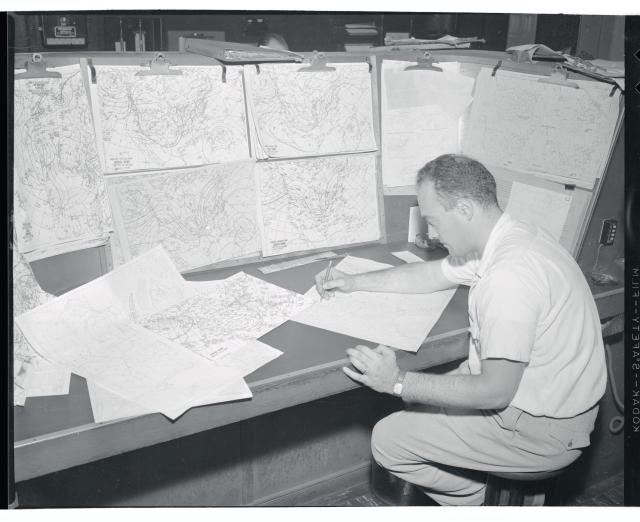 <p>Milton J. Fayne, meteorologist at the New York Weather Bureau, scans a large number of weather charts to get a line on the activities of Hurricane Hazel, the killer hurricane that smashed the island of Haiti. Fayne said the hurricane posed a definite threat to the mid-Atlantic and New England portions of the country but stated it was still too early to determine how great its impact would be. Along the coast of North Carolina, residents and fishermen moved boats inland, boarded up stores and some took refuge in solidly built Coast Guard stations. (Photo from Getty Images) </p>