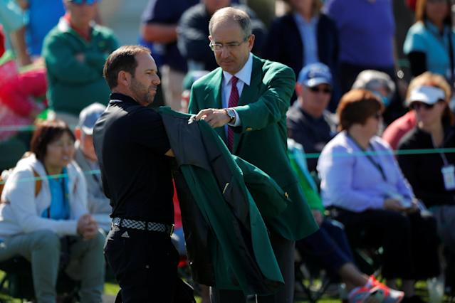 Brian Roberts, CEO of Comcast and Augusta National member, helps Masters champion Sergio Garcia with his green jacket, as they watch the Drive, Chip and Putt National Finals at Augusta National Golf Club in Augusta, Georgia, U.S., April 1, 2018. REUTERS/Brian Snyder