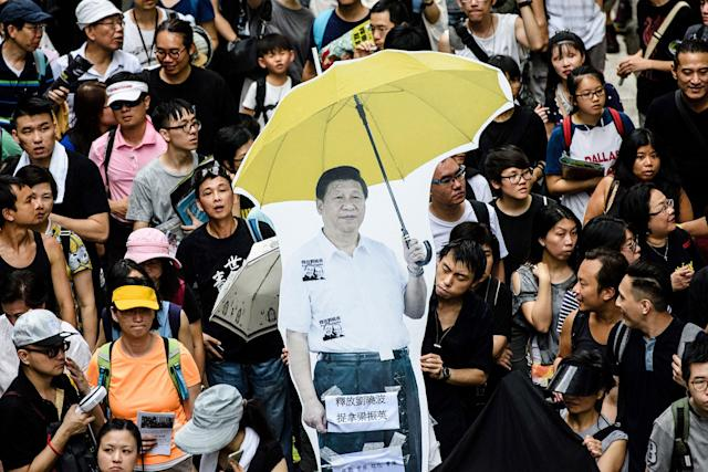 <p>A cardboard cut-out of China's President Xi Jinping (C) holding a yellow umbrella, a symbol of the 2014 'Umbrella Movement', is carried during a protest march in Hong Kong on July 1, 2017, coinciding with the 20th anniversary of the city's handover from British to Chinese rule. (Photo: Anthony WallaceAFP/Getty Images) </p>