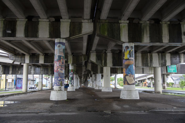"""The elevated freeway running along Claiborne Avenue in New Orleans crosses over Dumaine Street in this photo taken on May 11, 2021. Black businesses and culture thrived under a canopy of oak trees along Claiborne Avenue until the late 1960s, until the freeway was built directly on top of it — ripping up the trees and tearing apart a street sometimes called the """"Main Street of Black New Orleans."""" (AP Photo/Rebecca Santana)"""
