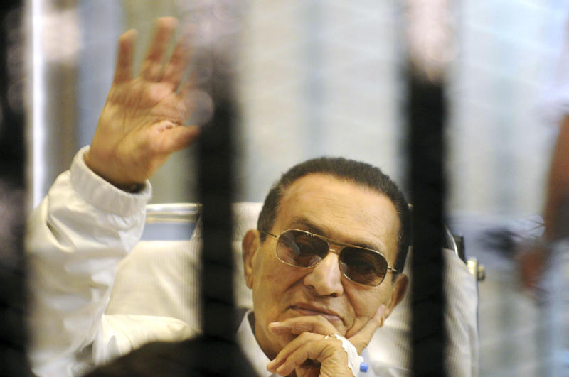 FILE - In this Saturday, April 13, 2013 file photo, former Egyptian President Hosni Mubarak waves to his supporters from behind bars as he attends a hearing in his retrial on appeal in Cairo, Egypt. An Egyptian security official said Saturday, Feb. 8, 2014, the retrial of Egypt's deposed President Mubarak was abruptly halted because of a sudden health scare. (AP Photo, File)
