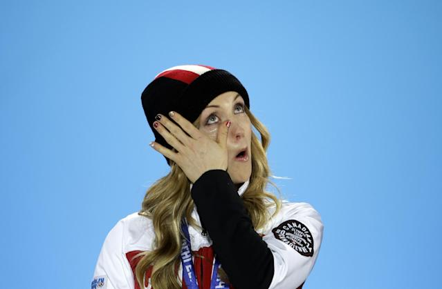 Women's moguls gold medalists Canada's Justine Dufour-Lapointe wipes a tear away following the playing of Canada's national anthem during the medal ceremony at the 2014 Winter Olympics, Sunday, Feb. 9, 2014, in Sochi, Russia. (AP Photo/David Goldman)