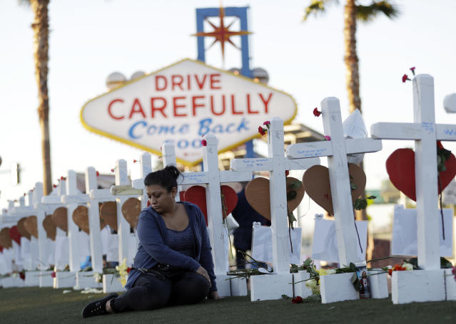 <p>Cece Navarrette sits near a cross for her cousin, Bailey Schweitzer, who was among those killed during the mass shooting Friday, Oct. 6, 2017, in Las Vegas. (Photo: Gregory Bull/AP) </p>