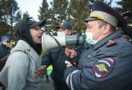 A woman argues with police officer during a protest in support of jailed opposition leader Alexei Navalny in Ulan-Ude, the regional capital of Buryatia, a region near the Russia-Mongolia border, Russia, Wednesday, April 21, 2021. Navalny's team has called for nationwide protests on Wednesday following reports that the politician's health was deteriorating in prison, where he has been on hunger strike since March 31. Russian authorities have stressed that the demonstrations were not authorized and warned against participating in them. (AP Photo/Anna Ogorodnik)