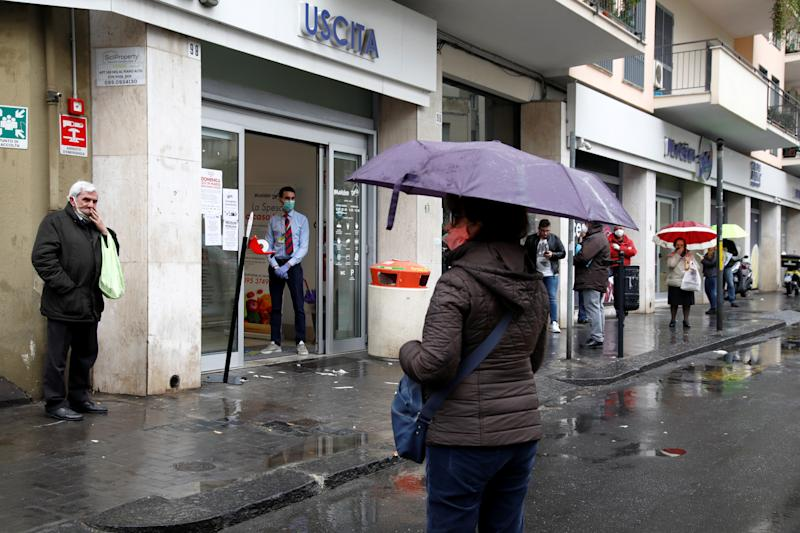 People line up in the rain outside a supermarket after the Italian island of Sicily closed them on Sunday, as it tightens measures to try and contain the spread of coronavirus disease (COVID-19), in Catania, Italy March 23, 2020. REUTERS/Antonio Parrinello