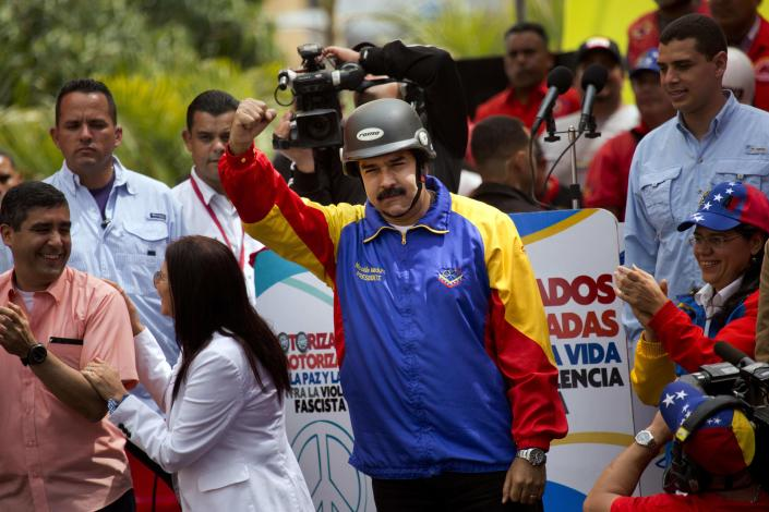FILE - In this Feb. 24, 2014, file photo, a helmet wearing Venezuelan President Nicolas Maduro cheers motorcyclists during a rally in support of his government in Caracas, Venezuela. Since Feb. 12, opponents of President Nicolas Maduro have been staging countrywide protests that the government says have resulted in scores of deaths and more than more than a hundred injured. The demonstrators blame Maduro's administration for the country's high crime rate and economic troubles. (AP Photo/Rodrigo Abd)