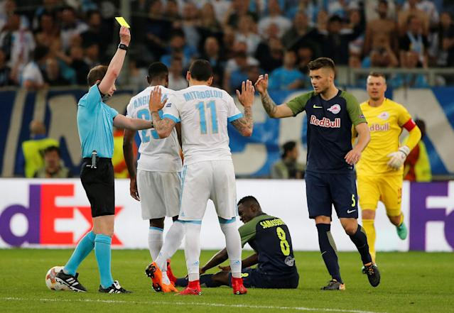 Soccer Football - Europa League Semi Final First Leg - Olympique de Marseille vs RB Salzburg - Orange Velodrome, Marseille, France - April 26, 2018 Marseille's Konstantinos Mitroglou is shown a yellow card by referee William Collum REUTERS/Jean-Paul Pelissier