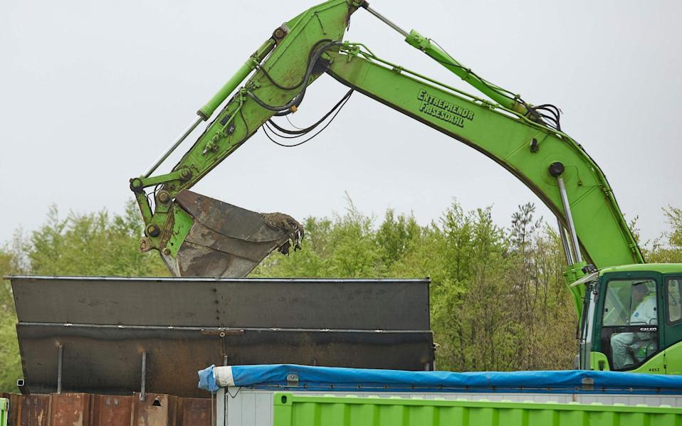 A excavator loads in a container buried mink for incineration during a trial excavation at a military area close to Norre Felding, Holstebro, - AFP
