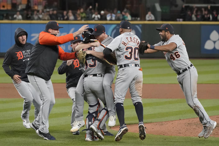 Detroit Tigers starting pitcher Spencer Turnbull, center, hugs catcher Eric Haase as teammates rush in after Turnbull threw a no hitter baseball game against the Seattle Mariners, Tuesday, May 18, 2021, in Seattle. The Tigers won 5-0. (AP Photo/Ted S. Warren)