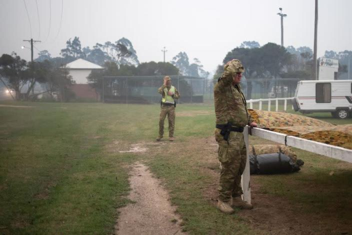 Members of a military support team deploy a tent as smoke begins to blanket the town of Eden