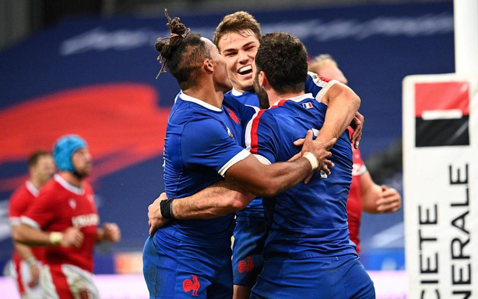 France's flanker Charles Ollivon (R) celebrates with wing Teddy Thomas (L) and scrum-half Antoine Dupont after scoring a try - AFP