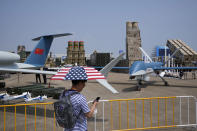 A man carrying an umbrella with the United States flag colors passes near Chinese made drones and anti-air missile systems displayed during the 13th China International Aviation and Aerospace Exhibition, also known as Airshow China 2021, on Sept. 28, 2021 in Zhuhai in southern China's Guangdong province. Nine months into U.S. President Joe Biden's administration, there are signs of movement in what has been a fraught U.S.-China relationship. (AP Photo/Ng Han Guan)