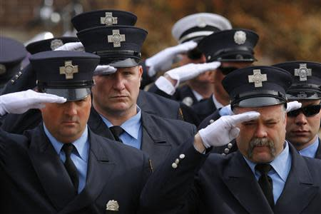 Firefighters salute during the funeral procession for Boston Fire Department Lieutenant Edward Walsh outside Saint Patrick's Church in Watertown