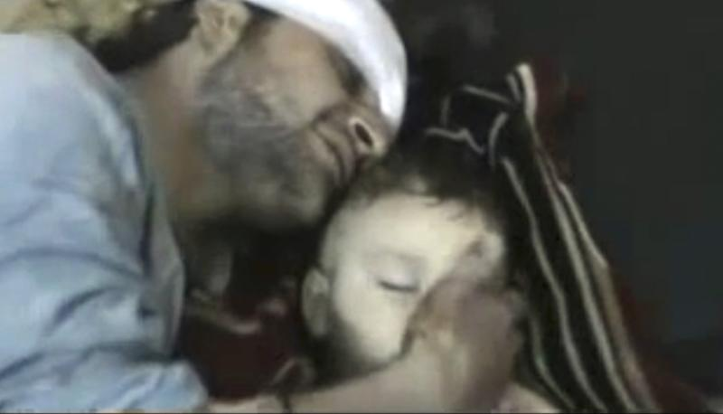 This Saturday, Feb. 18, 2012 image taken from amateur video made available by the Shaam News Network Wednesday, Feb. 22, 2012, shows a man touching the face of his son, who was purportedly killed by Syrian government shelling in Homs Syria. (AP Photo/Shaam News Network) THE ASSOCIATED PRESS CANNOT INDEPENDENTLY VERIFY THE CONTENT, DATE, LOCATION OR AUTHENTICITY OF THIS MATERIAL.