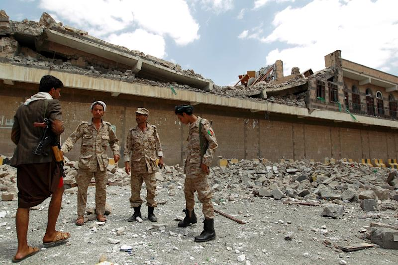 Yemeni armed forces loyal to the Huthi Shiite militia and a Huthi fighter (L) stand next to the rubble of a destroyed building following air strikes by the Saudi-led coalition on September 16, 2015 in the capital Sanaa