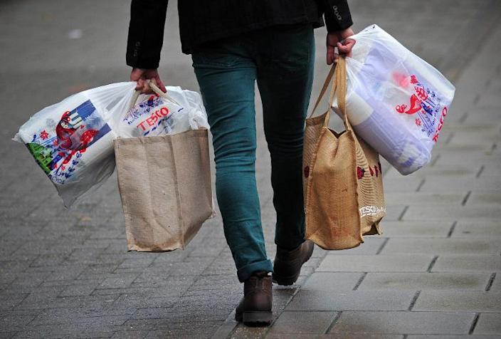 A man carries his shopping after visiting a Tesco store in south London, on October 2, 2013 (AFP Photo/Carl Court)