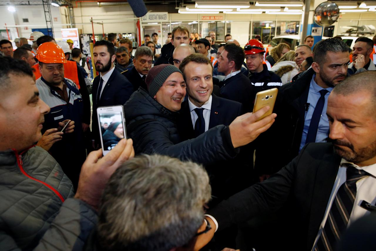 French President Emmanuel Macron poses for a selfie with an employee during Toyota's automobile manufacturing plant in Onnaing, France, January 22, 2018.  REUTERS/Pascal Rossignol