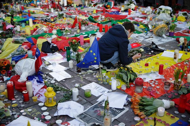 A boy lights a candle at a makeshift memorial on the Place de la Bourse in Brussels on March 23, 2016 (AFP Photo/Kenzo Tribouillard)