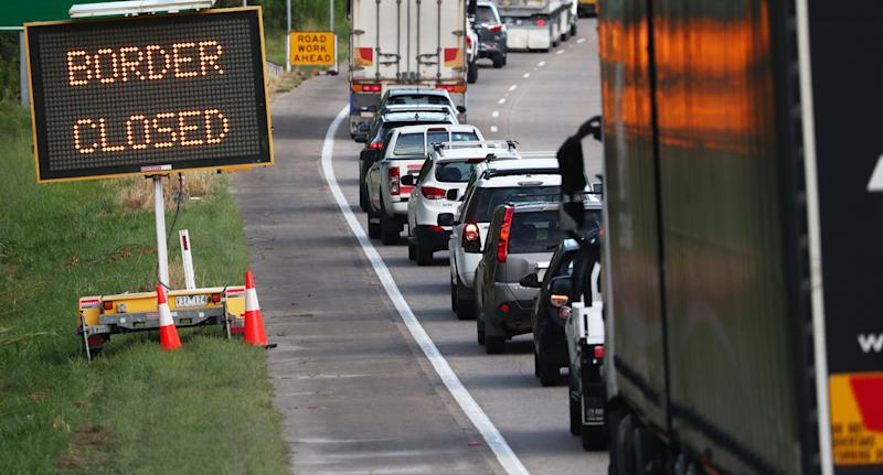 Photo shows a huge queue of cars and a 'border closed' sign.
