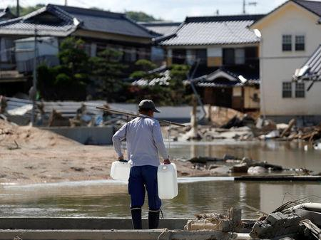 A local resident carries waters near submerged and destroyed houses in a flooded area in Mabi town in Kurashiki, Okayama Prefecture, Japan, July 9, 2018. REUTERS/Issei Kato
