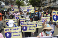 ADDS INFORMATION ON THE SIGNS - Anti-coup protesters hold signs showing support for a civilian-formed federal army during a protest march in Yangon, Myanmar, Saturday, April 3, 2021. Threats of lethal violence and arrests of protesters have failed to suppress daily demonstrations across Myanmar demanding the military step down and reinstate the democratically elected government. (AP Photo)