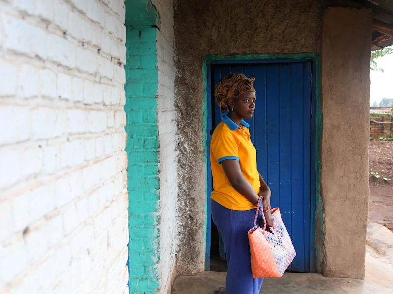 Outside the house she shares with her mother, Angel walks down the street to buy sugar in Ngoma Sector, Rwanda, in the southern part of the country near Huye (formerly known as Butare): Photography by Whitney Shefte