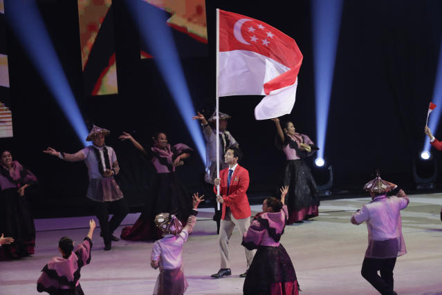 Singaporean squash athlete Samuel Kang holds their flag during the opening ceremony of the 30th South East Asian Games at the Philippine Arena, Bulacan province, northern Philippines on Saturday, Nov. 30, 2019. (AP Photo/Aaron Favila)