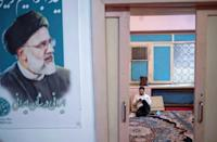 A supporter of Iranian President-elect Ebrahim Raisi checks his phone at one of his campaign offices in downtown Tehran