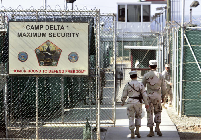 FILE - In this June 27, 2006 file photo, reviewed by a U.S. Department of Defense official, U.S. military guards walk within Camp Delta military-run prison, at the Guantanamo Bay U.S. Naval Base, Cuba. The White House says it intends to shutter the prison on the U.S. base in Cuba, which opened in January 2002 and where most of the 39 men still held have never been charged with a crime. (AP Photo/Brennan Linsley, File)
