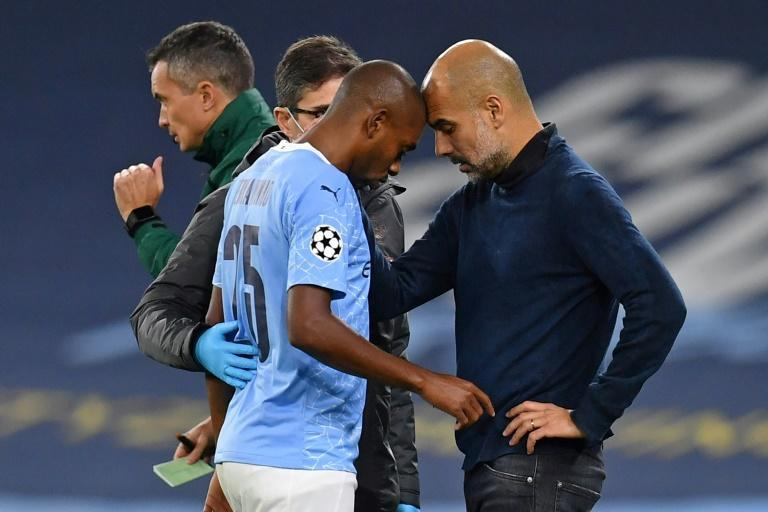 Manchester City manager Pep Guardiola (right)bemoaned losing Fernandinho (left)to injury