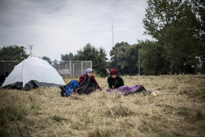 Women sit in the grass on September 22, 2015 outside the Opatovac transit center for migrants and refugees (AFP Photo/Federico Scoppa)