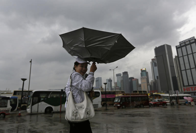 A woman braves strong wind near the waterfront in Hong Kong Sunday, Sept. 22, 2013. The year's most powerful typhoon had Hong Kong in its crosshairs on Sunday after sweeping past the Philippines and Taiwan and pummeling island communities with heavy rains and fierce winds. Typhoon Usagi was grinding westward and expected to make landfall close to Hong Kong late Sunday or early Monday. (AP Photo/Vincent Yu)