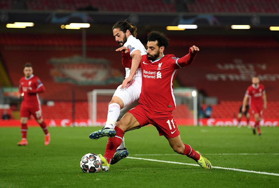LIVERPOOL, ENGLAND - APRIL 14:  Mohamed Salah of Liverpool is challenged by Isco of Real Madrid during the UEFA Champions League Quarter Final Second Leg match between Liverpool FC and Real Madrid at Anfield on April 14, 2021 in Liverpool, England. Sporting stadiums around the UK remain under strict restrictions due to the Coronavirus Pandemic as Government social distancing laws prohibit fans inside venues resulting in games being played behind closed doors.  (Photo by Shaun Botterill/Getty Images)