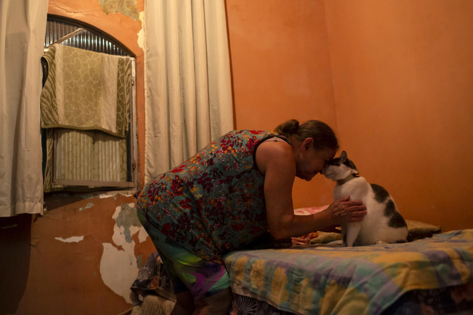 Diana dos Santos, 71, cuddles with her cat Pepinha, her only companion as she lives in social isolation in her home in the Mare neighborhood of Rio de Janeiro, Brazil, Friday Aug. 27, 2021, amid the new coronavirus pandemic. She refuses to leave her home until she gets a booster of the COVID-19 vaccine. (AP Photo/Bruna Prado)